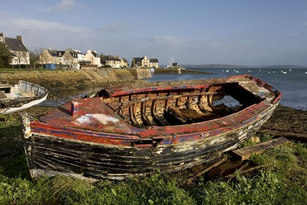 old boat on shore by harbour