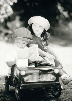 Children - boy and girl in toy car reading map