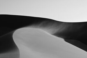 Dunes in late afternoon light - with sand blowing over the crest in a 'smoke