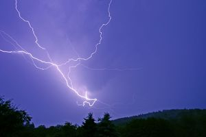 Lightning and thunder clouds - over woodland at night