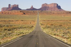 Monument Valley's long straight road (US 163) leading across flat desert towards sandstone buttes and pinnacles of rock