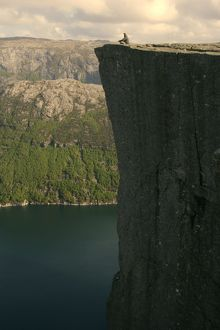 landscapes/preikestolen person meditating near edge rock