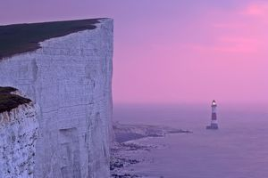 UK - lighthouse at Beachy Head with steep chalk cliffs at sunrise.