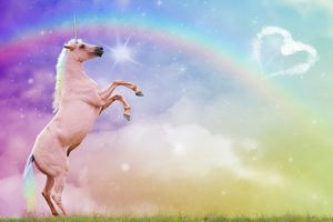 Unicorn rearing with fantasy rainbow clouds and heart